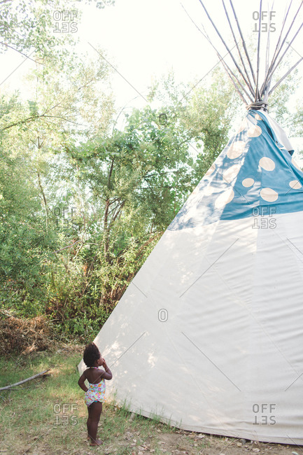 Toddler girl looking at a teepee tent