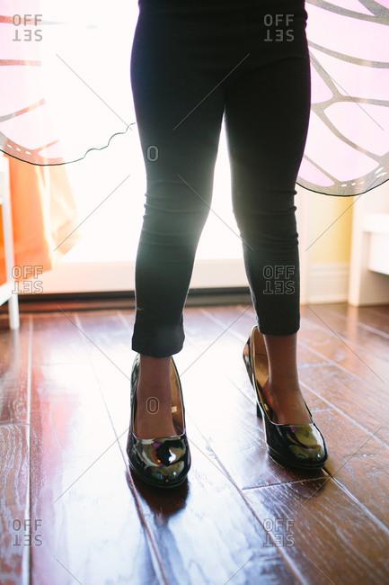 Little girl standing in woman's high heels