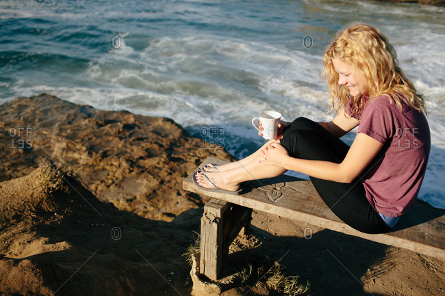 Young woman drinking coffee on a seaside bench