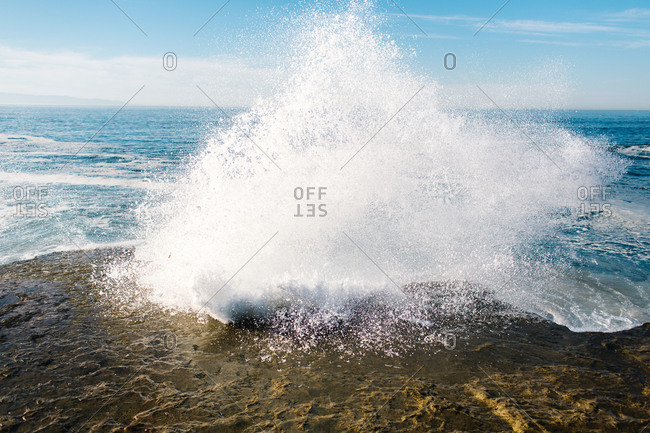 Large wave crashing on a rocky shore