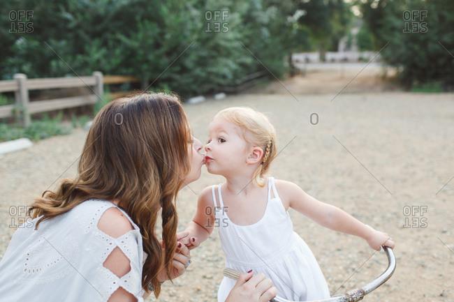 Mother kissing little girl on a bike