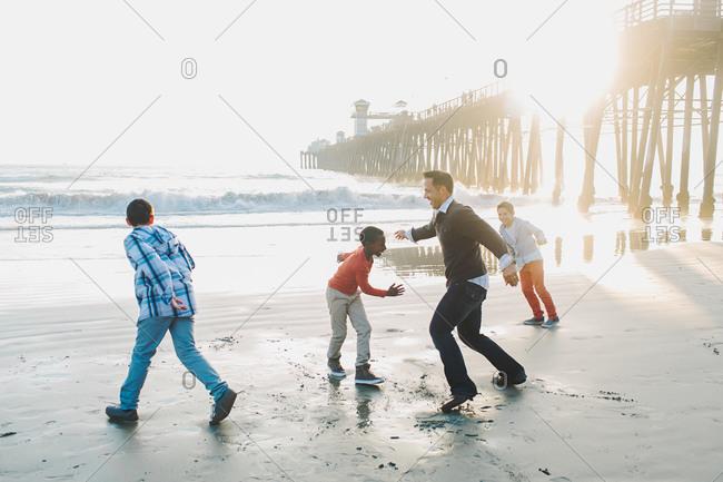 Man running on the beach with three boys