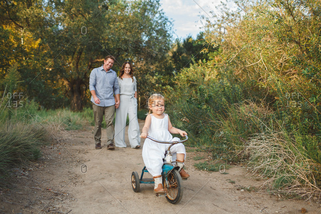 Parents following little girl riding tricycle