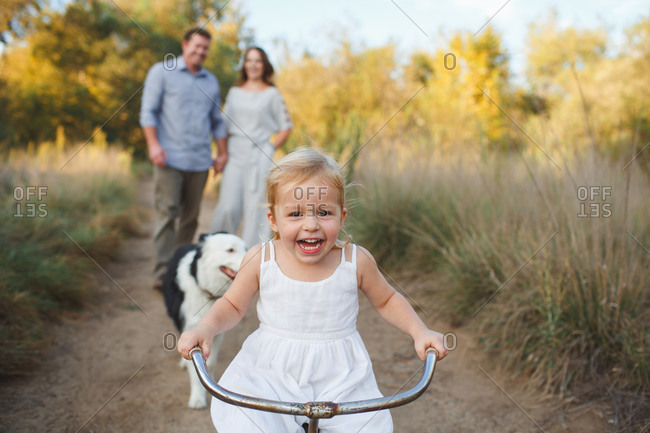 Little girl riding tricycle while dog and parents follow