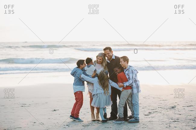 Blended family hugging on the beach