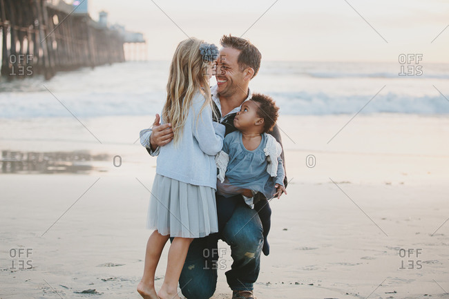 Father standing with two daughters on the beach
