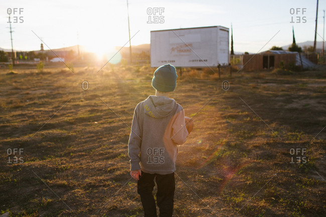 Boy walking in a field with a football