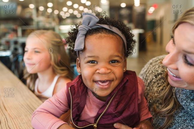 Woman holding smiling toddler girl