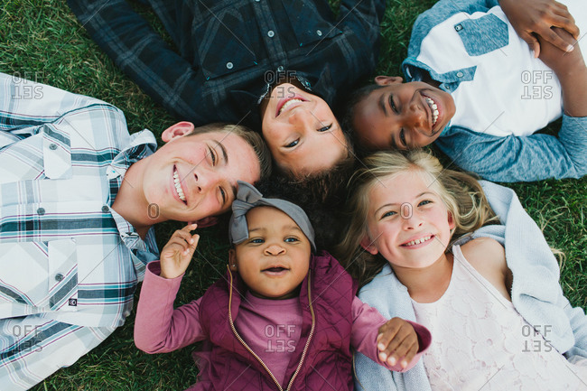 Overhead view of blended family lying in the grass