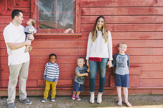 Blended family standing by a red building