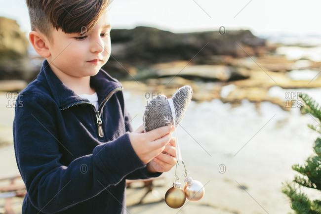 Boy holding heart with Christmas bulbs