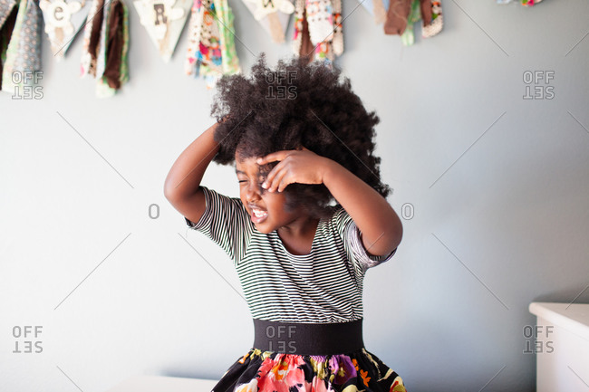 Little girl with afro hairstyle shaking her head