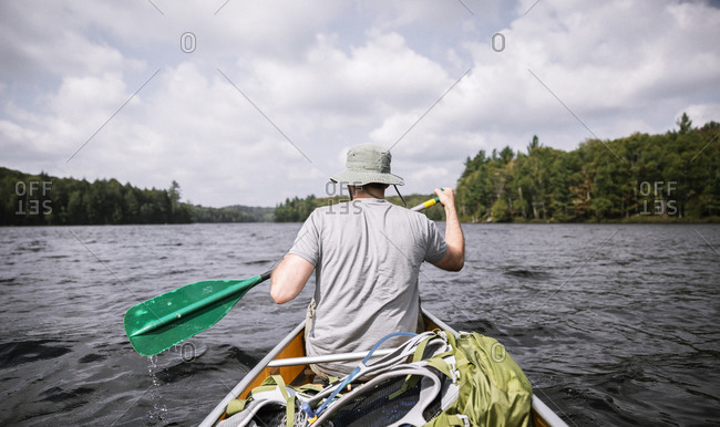 Man canoeing in a lake in Upstate, New York