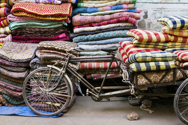 Mattresses and pillows by bicycle cart on street