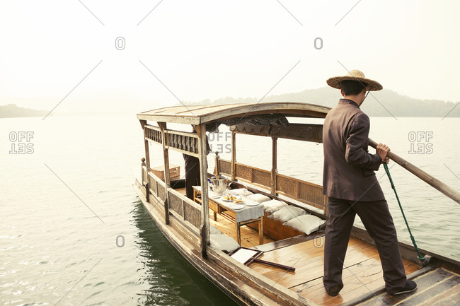 Rear view of man rowing traditional boat on river