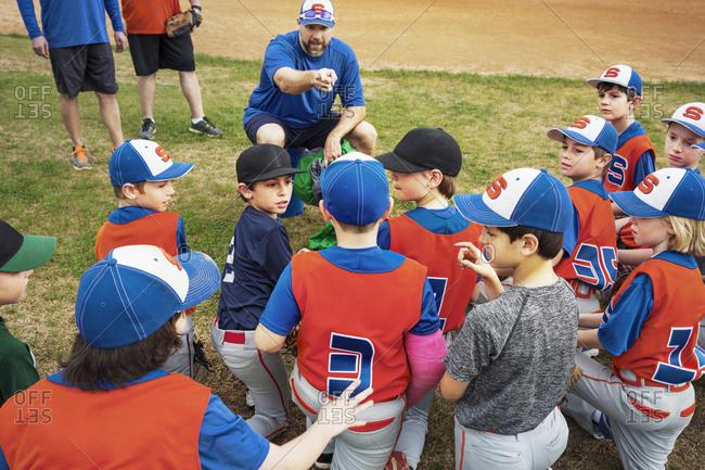 Baseball coach instructing boys on field