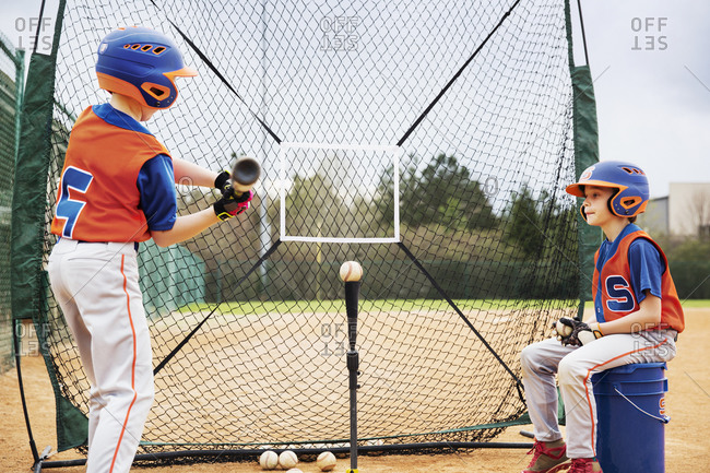 Boy looking at friend playing baseball on field