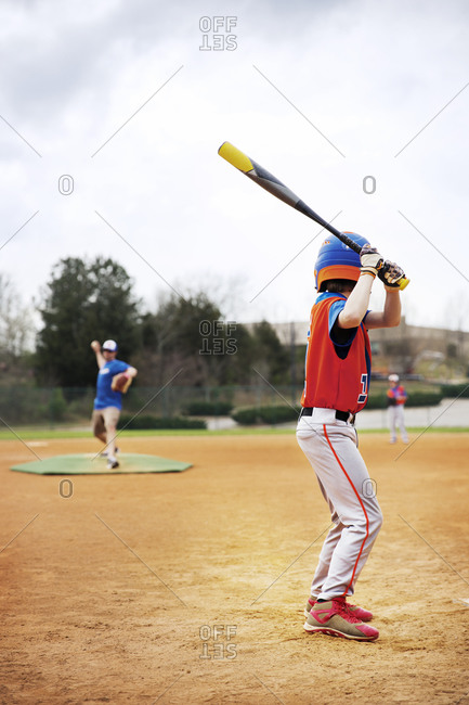 Side view of boy playing baseball with coach on field against sky