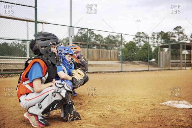Side view of baseball catchers crouching on field