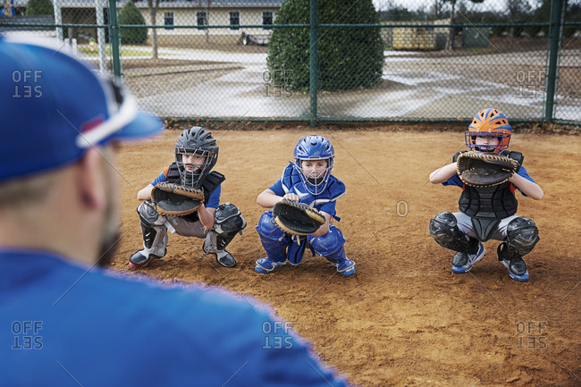 Rear view of coach training baseball catchers on field