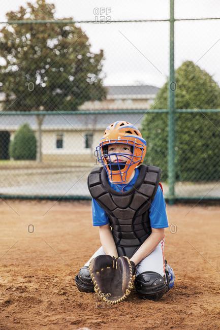 Baseball catcher kneeling on field