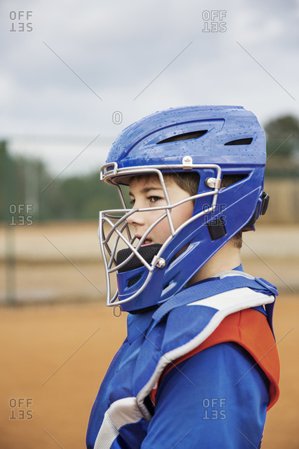 Side view of baseball catcher standing on field