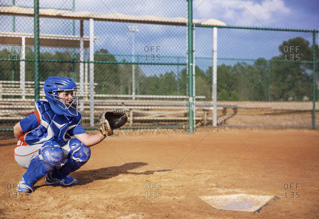 Baseball catcher crouching on field