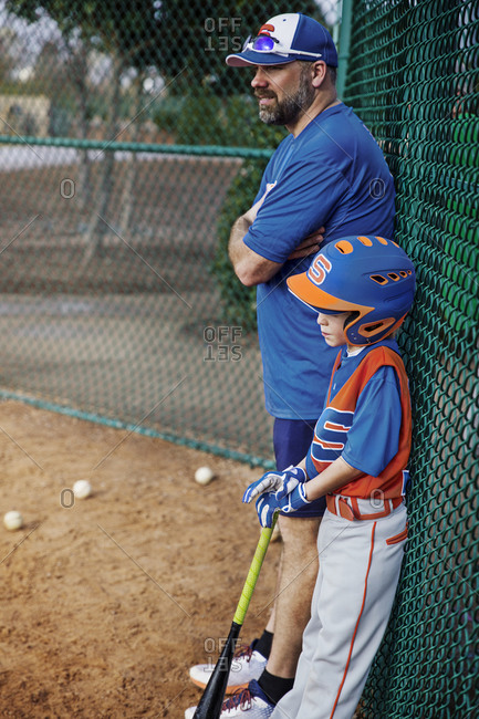 Side view of thoughtful baseball player and coach standing by chain-link fence on field
