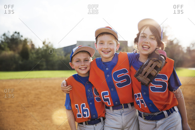 Portrait of happy baseball players standing on field