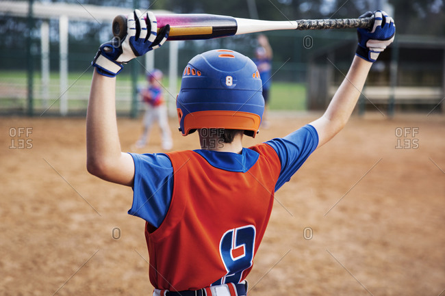 Rear view of boy holding baseball bat on field