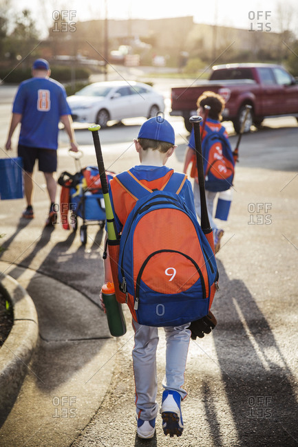 Rear view of boys and baseball coach walking on street