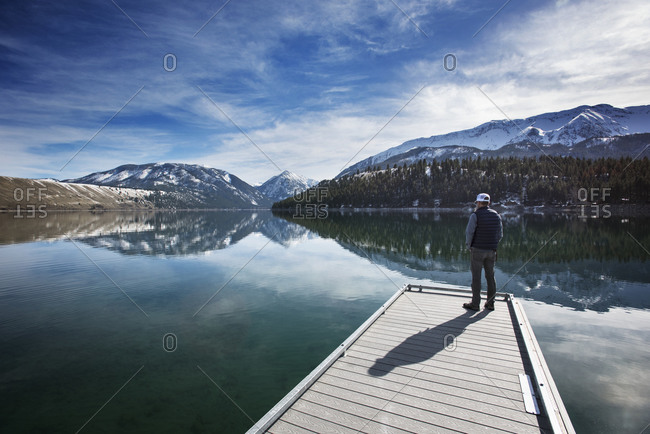 Rear view of man looking at Wallowa Mountains while standing on pier
