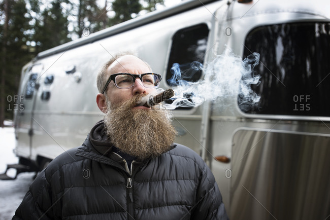 Thoughtful mature man smoking cigar outside caravan in forest