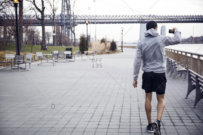 Rear view of male athlete photographing Williamsburg Bridge while walking on footpath