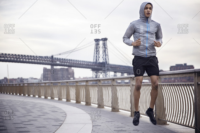 Determined male athlete running on footpath with Williamsburg Bridge in background