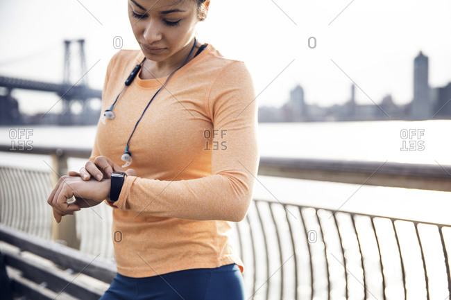 Female runner checking the time while standing on footpath with Williamsburg Bridge in background