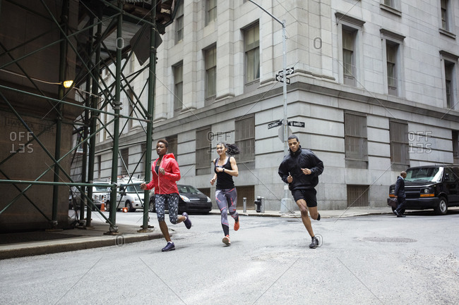 Determined athletes jogging on city street