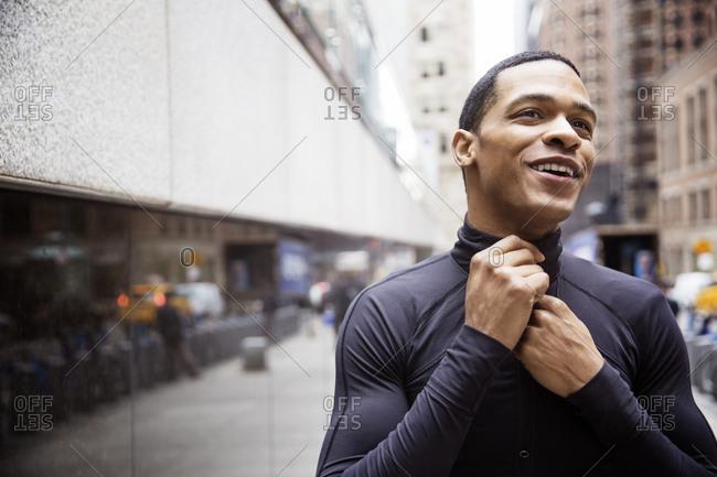 Happy male athlete wearing jacket on city street