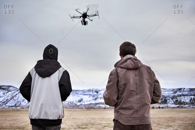 Rear view of father and son flying octocopter on field during winter