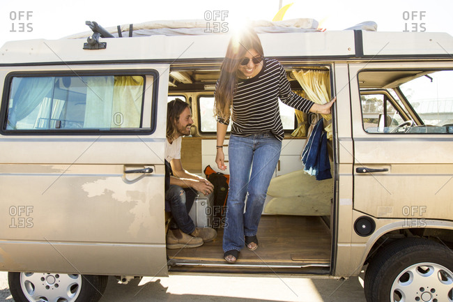 Happy woman disembarking mini van during vacation with man