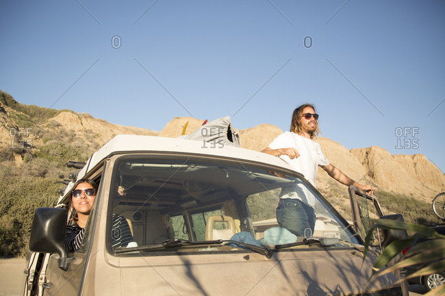 Young couple in mini van enjoying vacation against clear blue sky