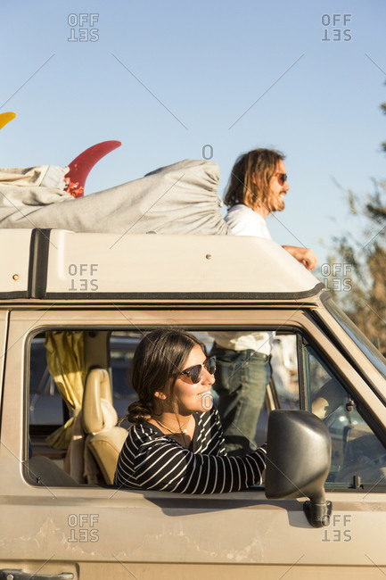 Couple in mini van enjoying vacation against clear sky