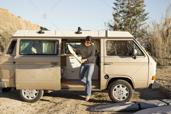 Woman holding surfboard while disembarking mini van during vacation