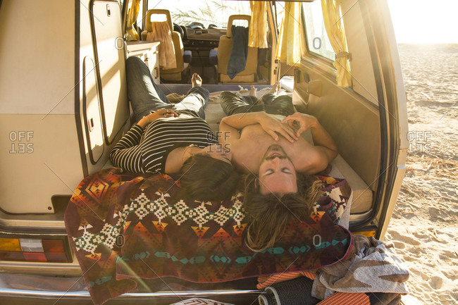 Romantic young couple lying in mini van during summer vacation on San Onofre State Beach