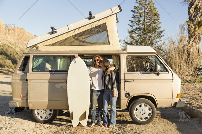Loving woman kissing man holding surfboard in front of mini van on San Onofre State Beach