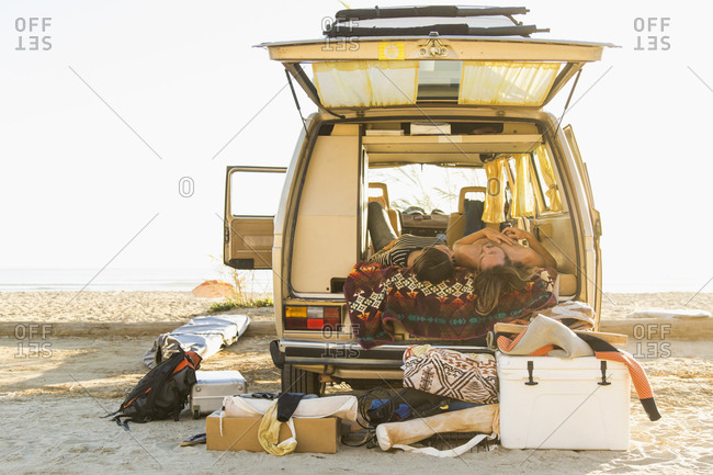 Young couple lying in mini van during summer vacation on San Onofre State Beach