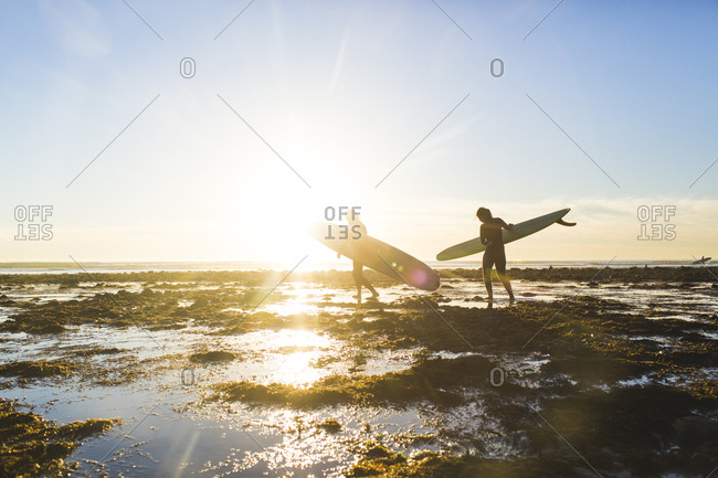 Couple carrying surfboards while walking on San Onofre State Beach during vacation