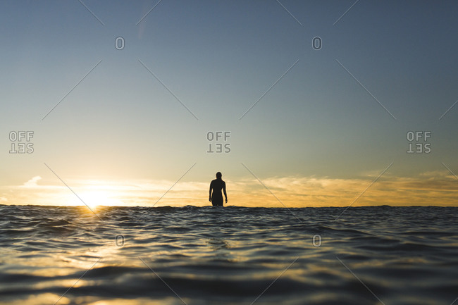 Distant view of female surfer on sea against sky during sunset