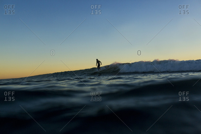 Distant view of silhouette man surfing on sea during sunset