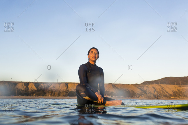 Young woman sitting on surfboard in sea against clear sky